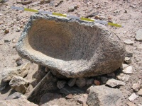 Heavily worn stone quern from UK001